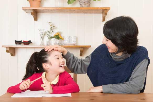 家庭学習で子供をほめている母親